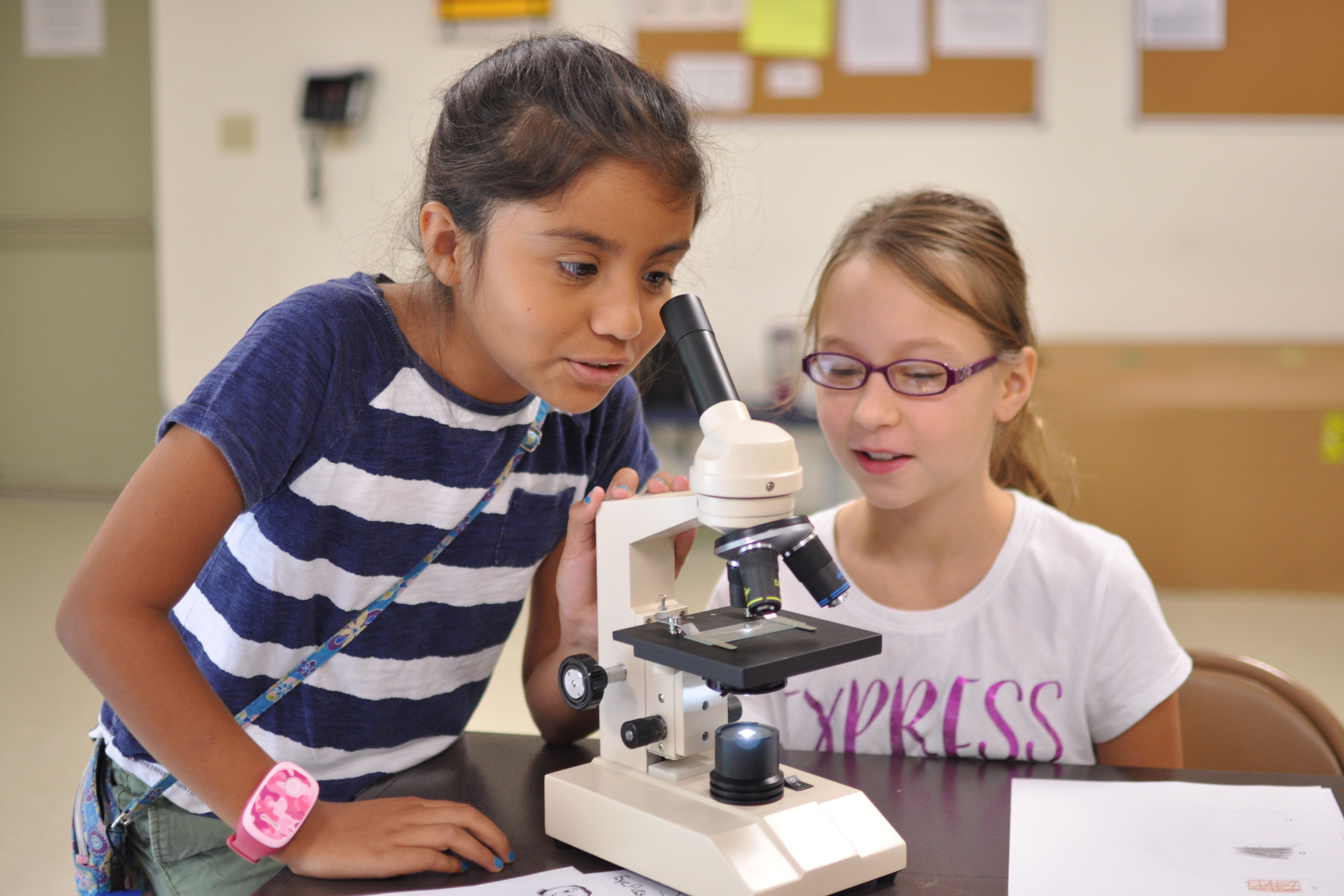 Aug 5, 2015-Marine Corps Base Quantico - Sofia, age 10, and Lael, age 11, take turns looking at hair fibers under a microscope, Photo By: Ida Irby, Public Domain