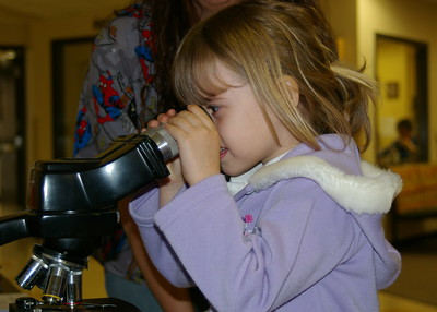 Four year old Lilly Dameron takes a look through a microscope by eagle102.net on Flickr.com, public domain, image unaltered, https://creativecommons.org/licenses/by/2.0/
